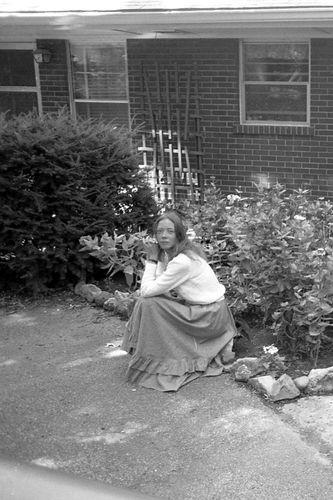 Carla sitting outside house