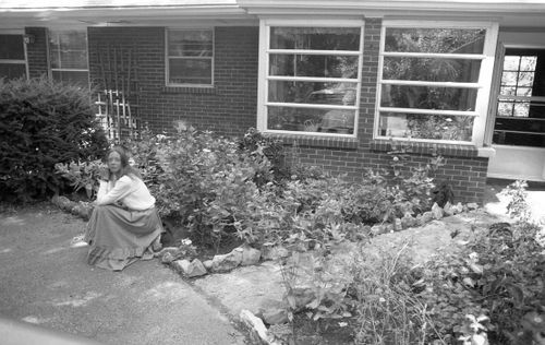 Wide angle of Carla sitting outside house
