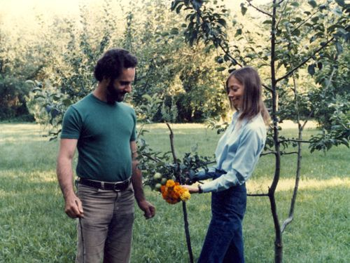 Carla and Jim outside with marigold flowers